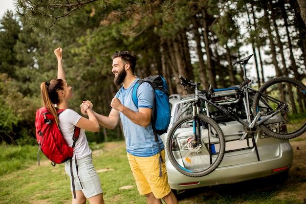 Jeune couple avec tenue de trekking debout dans la forêt