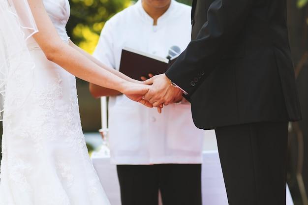 Jeune couple tient la main lors d'une cérémonie de mariage