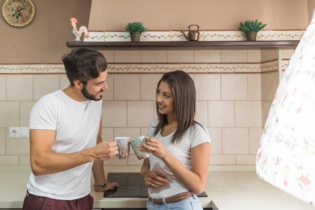 Jeune couple tinter les tasses dans la cuisine