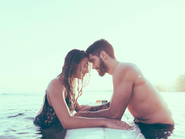 Jeune couple touchant les fronts près de la planche de surf