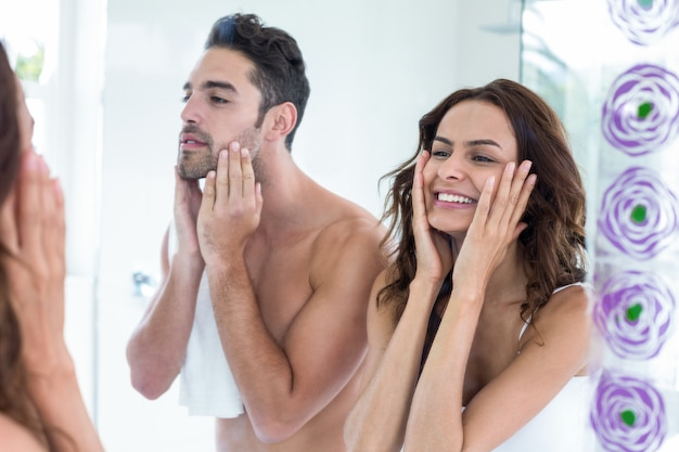 Jeune couple touchant le visage dans la salle de bain