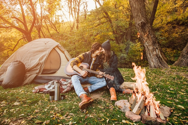 Jeune couple de touristes aimant se détendre près du feu de joie dans la nature