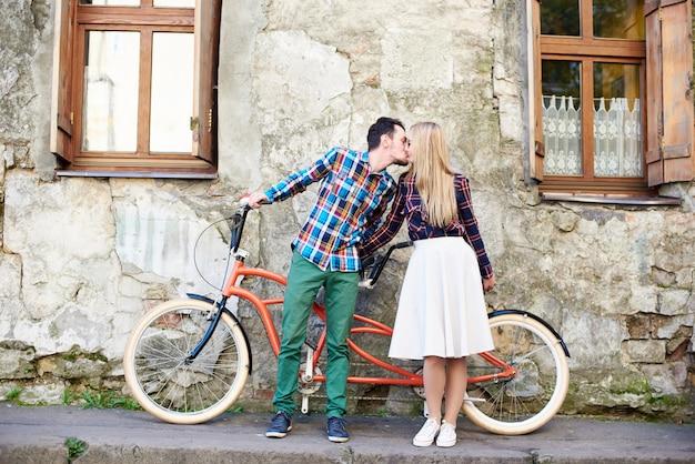 Jeune couple de touristes, bel homme et jolie femme blonde à vélo tandem le long de la rue.