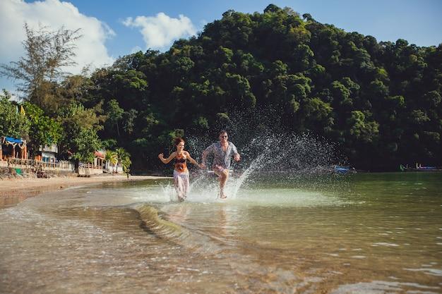 Jeune couple de touristes belle main dans la main courir ensemble le long du rivage de la plage avec les montagnes et l'eau de mer bleue et le ciel, à l'extérieur, créent des éclaboussures. mode de vie voyage et tourisme, lune de miel