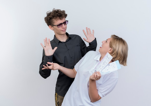 Jeune couple de touristes confus et mécontent de l'homme regardant sa petite amie avec des billets d'avion dans les mains debout sur un mur blanc