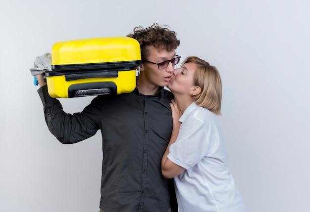 Jeune couple de touristes femme heureuse embrassant son petit ami avec valise debout sur un mur blanc