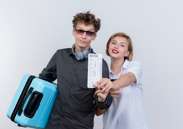 Jeune couple de touristes homme avec un casque tenant valise montrant les billets d'avion debout à côté de sa petite amie souriant confiant sur mur blanc
