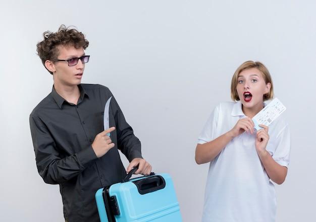 Jeune couple de touristes homme et femme tenant des billets d'avion et valise à la surprise et surpris debout sur un mur blanc