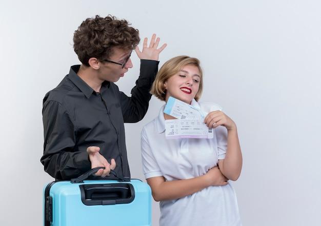 Jeune couple de touristes surpris man holding valise en regardant sa petite amie avec des billets d'avion en mains debout sur un mur blanc