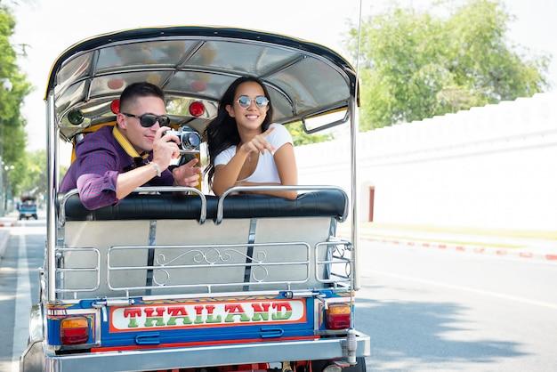 Jeune couple de touristes voyageant en taxi tuk tuk local à bangkok, thaïlande