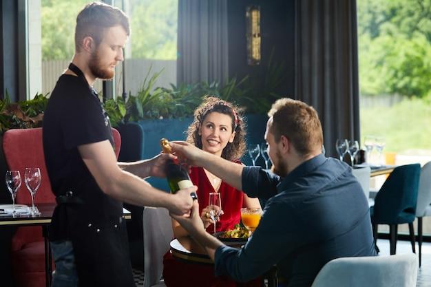 Jeune couple en train de dîner au restaurant serveur a apporté une bouteille de champagne