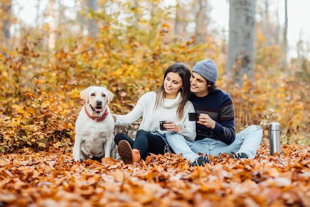 Jeune couple en train de pique-niquer avec leur labrador doré dans le parc, allongé sur une couverture.