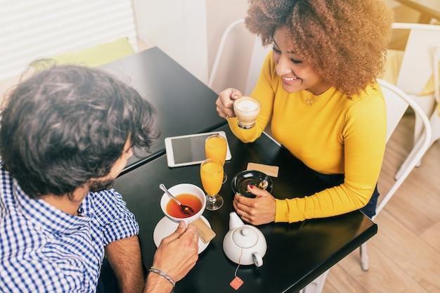 Jeune couple en train de prendre son petit déjeuner dans un café, boire du thé et du café. vue d'en-haut.