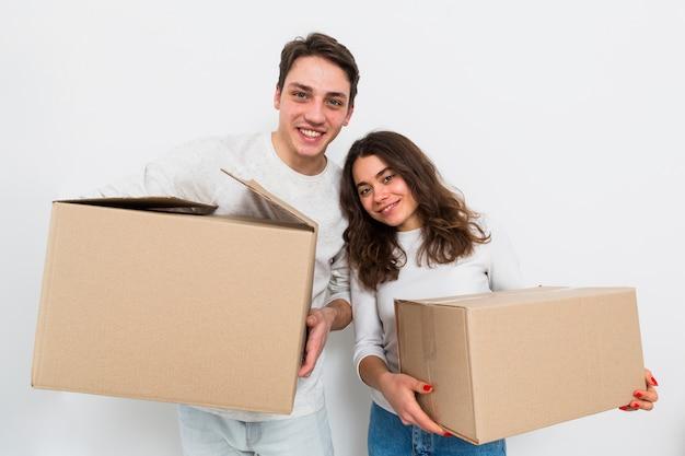 Jeune couple transportant des boîtes en carton à la main, isolé sur fond blanc