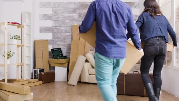 Jeune couple transportant des cartons dans leur nouvel appartement. jour de déménagement pour les propriétaires d'appartements.