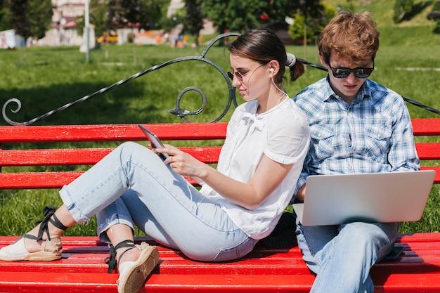 Jeune couple travaillant dans le parc
