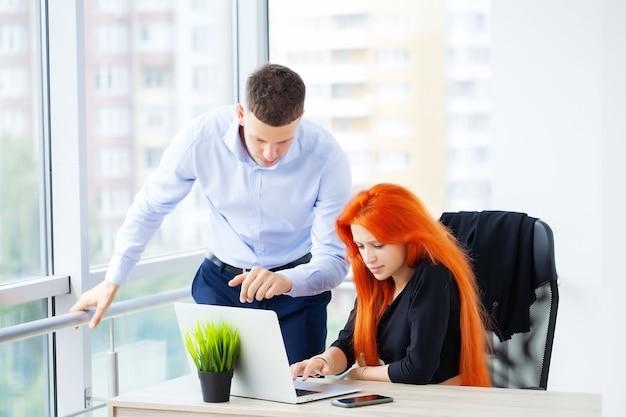 Jeune couple travaillant ensemble sur un ordinateur portable au bureau.