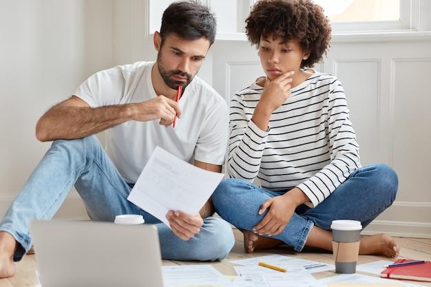 Jeune couple travaillant à la maison