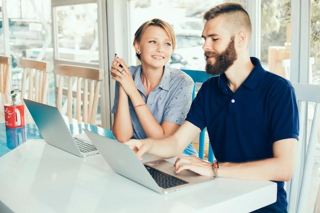 Jeune couple travaillant sur des ordinateurs portables dans un café faisant un projet, conférant, pigistes