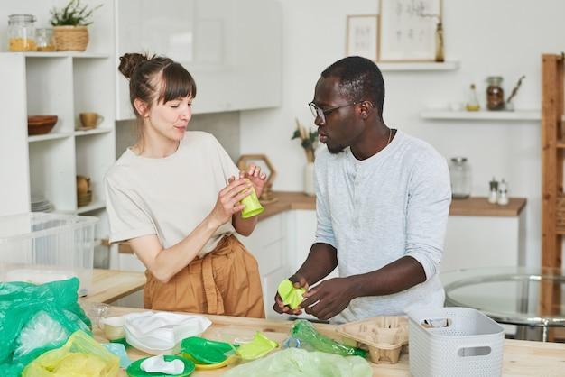 Jeune couple triant les ordures ensemble dans la cuisine à la maison