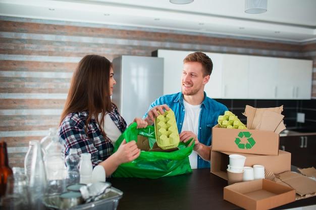 Un jeune couple trie les ordures dans la cuisine. jeune homme et femme trient les matières recyclables dans la cuisine. il y a du carton, du papier, du fer, du plastique et du verre et d'autres matériaux qui peuvent être recyclés.
