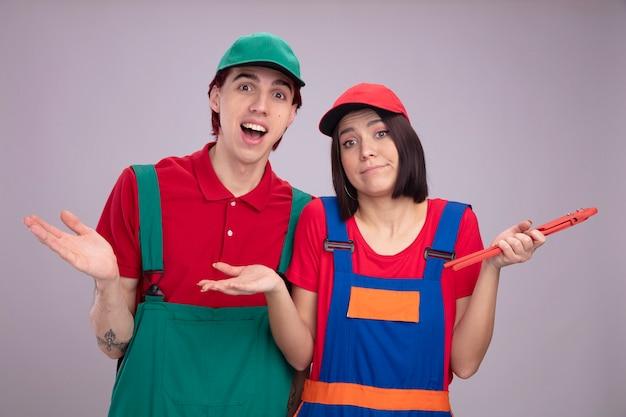 Jeune couple en uniforme de travailleur de la construction et casquette fille désemparée tenant une clé à tuyau mec excité à la fois regardant la caméra montrant une main vide isolée sur un mur blanc
