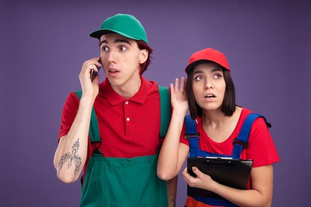 Jeune couple en uniforme de travailleur de la construction et casquette impressionné mec parlant au téléphone regardant côté curieux fille tenant le presse-papiers jusqu'à l'écoute de la conversation téléphonique isolée