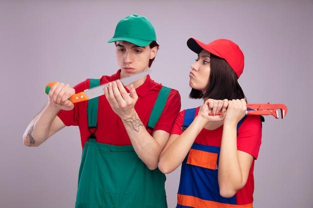 Jeune couple en uniforme de travailleur de la construction et casquette mec sérieux tenant et regardant la main vu bouder fille tenant une clé à pipe regardant mec isolé sur mur blanc