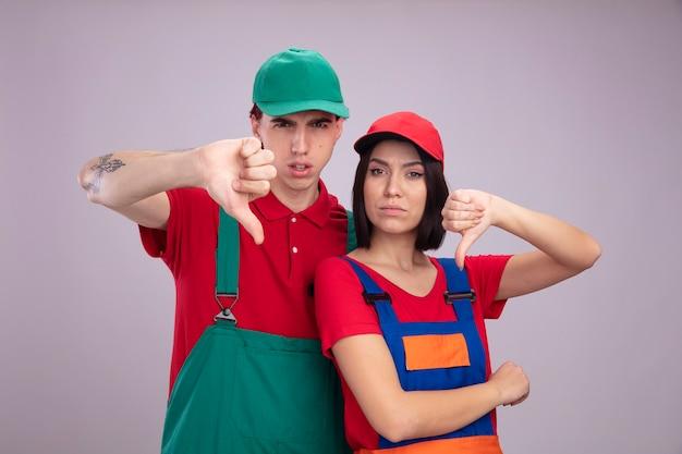 Jeune couple en uniforme de travailleur de la construction et chapeau fronçant les sourcils guy fille stricte montrant le pouce vers le bas