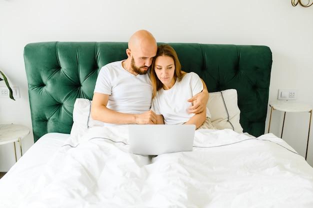 Jeune couple utilisant un ordinateur portable ensemble dans son lit.