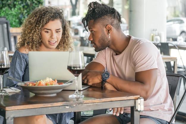 Jeune couple utilisant un ordinateur portable tout en déjeunant ensemble dans un restaurant.