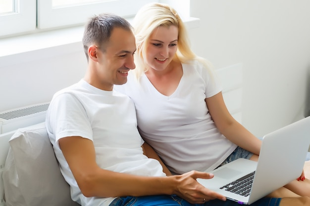 Jeune couple, utilisation, ordinateur portable, bureau, maison, penser