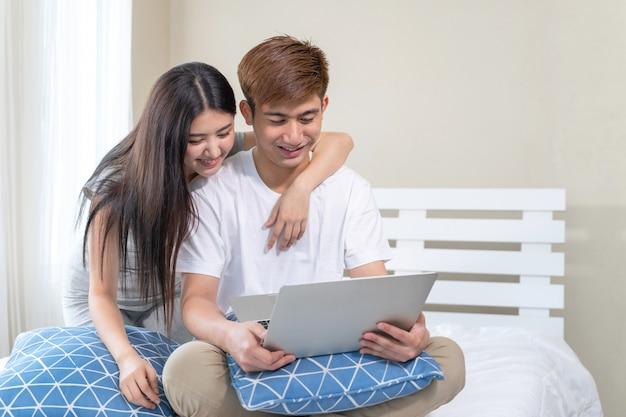 Jeune couple utilise un appareil technologique sur le lit