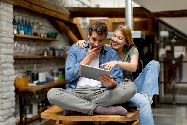 Jeune couple utilise une tablette numérique et souriant dans la cuisine à la maison