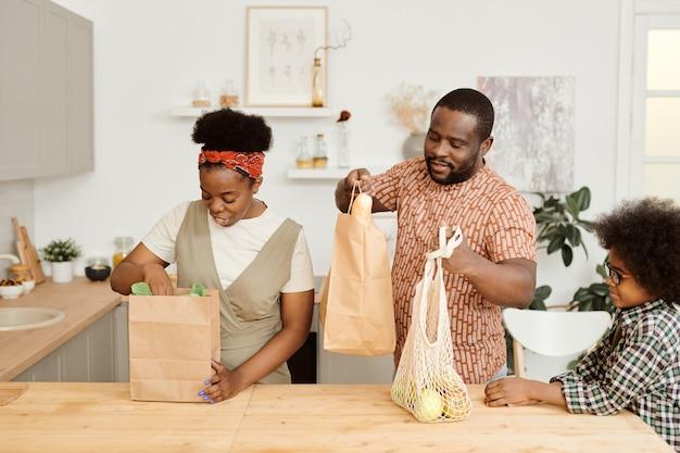 Jeune couple va sortir des produits alimentaires des sacs en papier