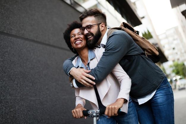 Jeune couple en vacances s'amusant à conduire un scooter électrique à travers la ville.