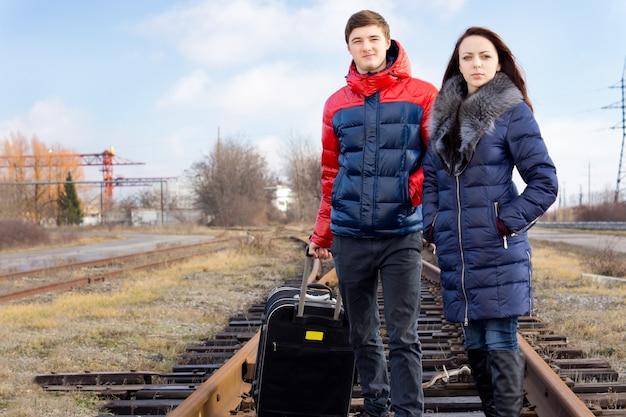 Jeune couple avec une valise attendant le train debout avec impatience au centre des voies sur les traverses en bois