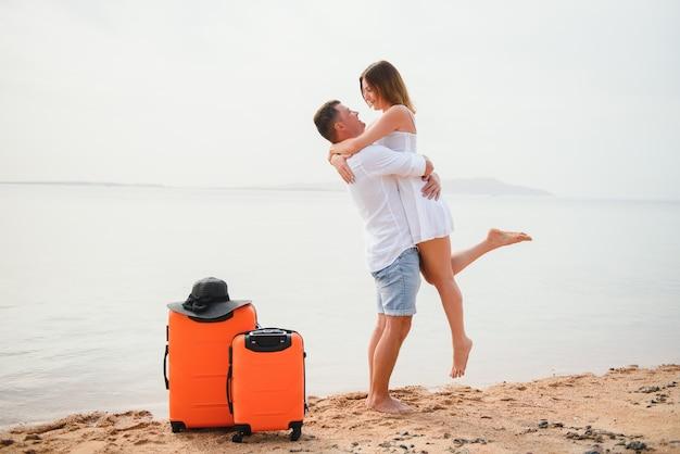 Jeune couple avec valise sur la plage en journée d'été
