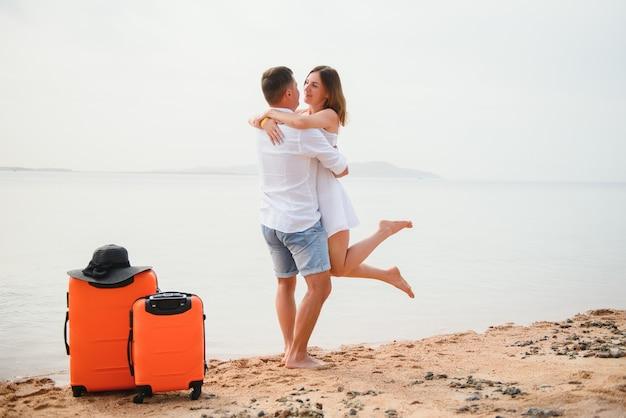 Jeune couple avec des valises sur la plage en journée d'été