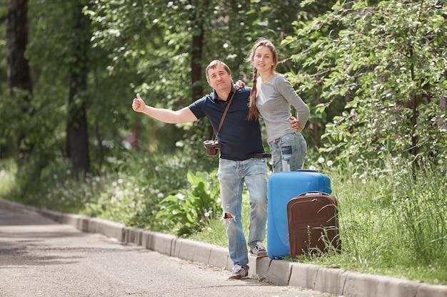 Jeune couple avec valises votant sur la route. le concept de l'auto-stop