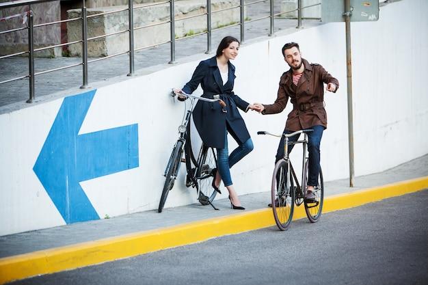 Jeune couple avec un vélo en face de la ville