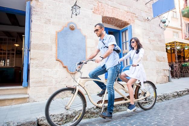 Jeune couple, sur, vélo tandem, rue, ville