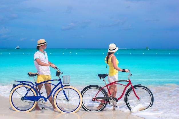 Jeune couple avec des vélos sur la plage de sable blanc