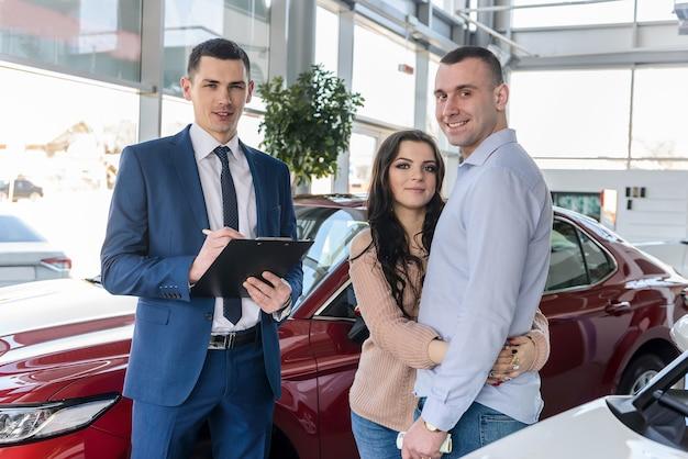 Jeune couple avec vendeur près de nouveau contrat de signature de voiture