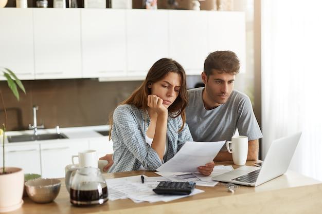 Jeune couple vérifiant leur budget familial