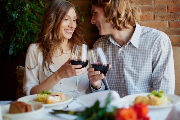 Jeune couple avec verres de vin rouge