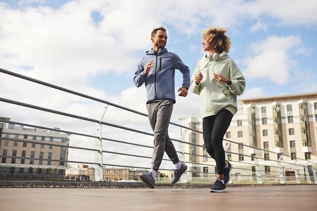 Jeune couple en vêtements de sport jogging ensemble sur la rue de la ville