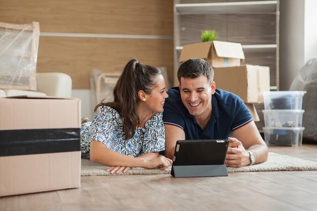 Un jeune couple vient d'emménager dans un nouvel appartement et achète en ligne des meubles avec une tablette dans les mains