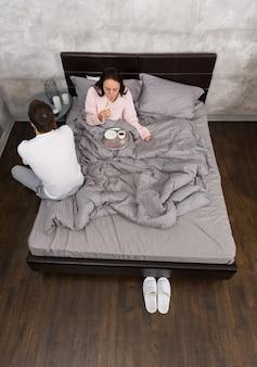 Un jeune couple vient de se réveiller et de prendre son petit-déjeuner au lit, en pyjama, dans la chambre de style loft