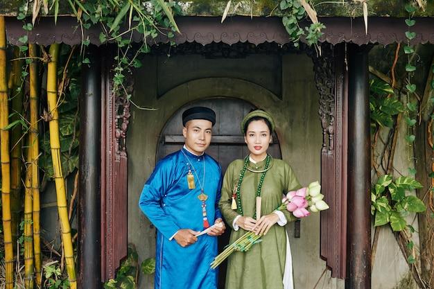 Jeune couple vietnamien dans de belles robes ao dai debout aux portes d'entrée du vieux bâtiment